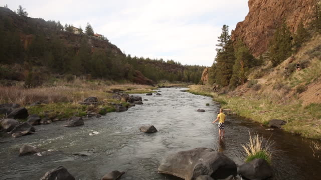 A young man fly fishing on the Crooked River in Smith Rock State Park.