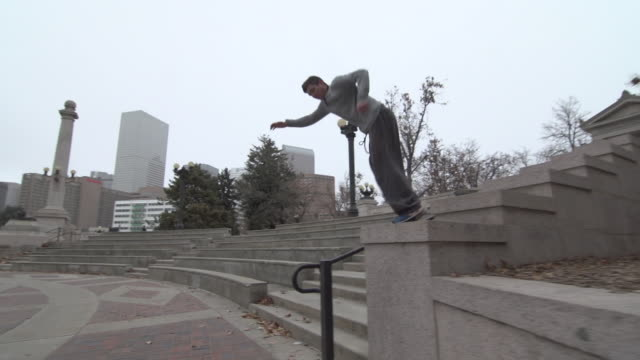 A young man freerunner doing parkour and flips in a city courtyard.  - Slow Motion