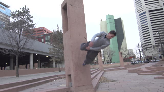 A young man freerunner doing parkour off steps and flips off of wall in downtown city park.  - Slow Motion