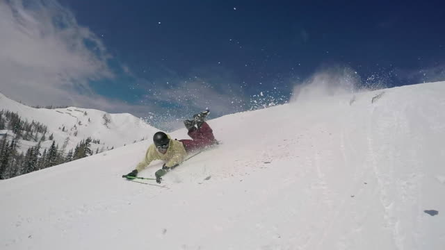 A young man freestyle skier crashes into snow while skiing off a jump in a terrain park.  - Slow Motion