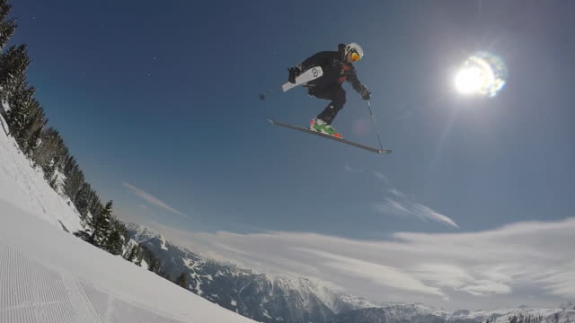 A young man freestyle skier skiing and going off jumps in a terrain park on a snow covered mountain.  - Slow Motion