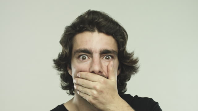 Young man gesturing speak no evil