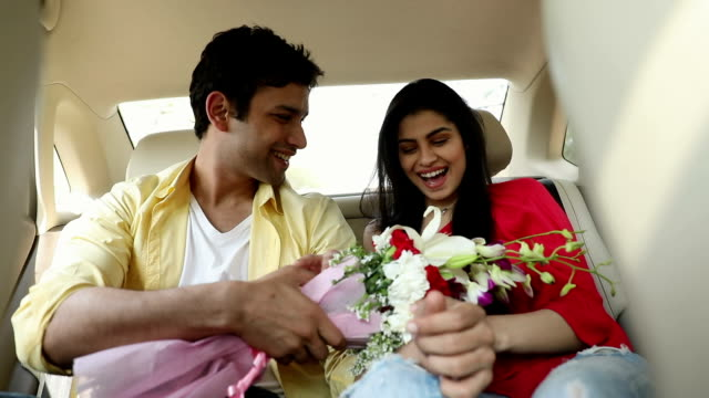 Young man giving bunch of flowers to his girlfriend, Delhi, India