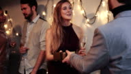 Young man giving gift to young woman during Christmas party