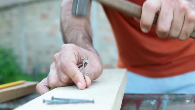 Young man hammering nails in wooden board
