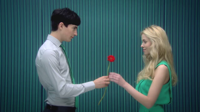 Young man handing flower to girlfriend