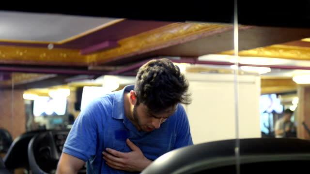 Young man having palpitation on the treadmill