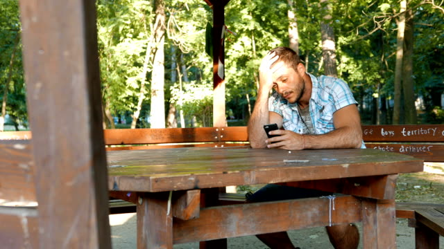 Young man having relationship problems texting on his smart phone