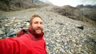 Young man hiking on glacier takes selfie portrait