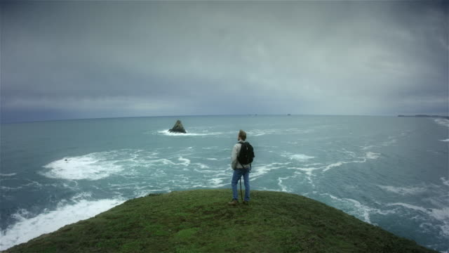 Young man hiking trail on Pacific Ocean