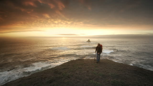 Young man hiking trail overlooking Pacific Ocean at sunset