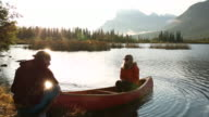 Young man holds canoe for woman, mountain lake