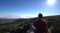 Young man in Cape Town on top of mountain looking at view