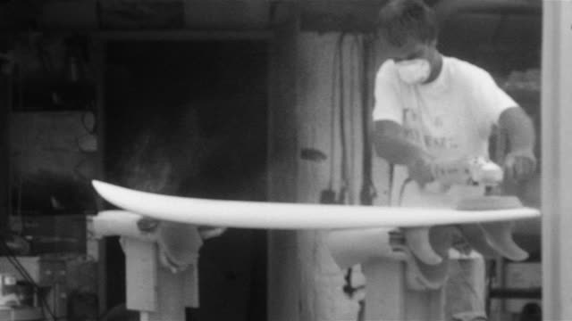 Young man in dust mask sanding surfboard