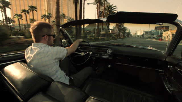 A young man in sunglasses cruises in a convertible down an empty street in Las Vegas.