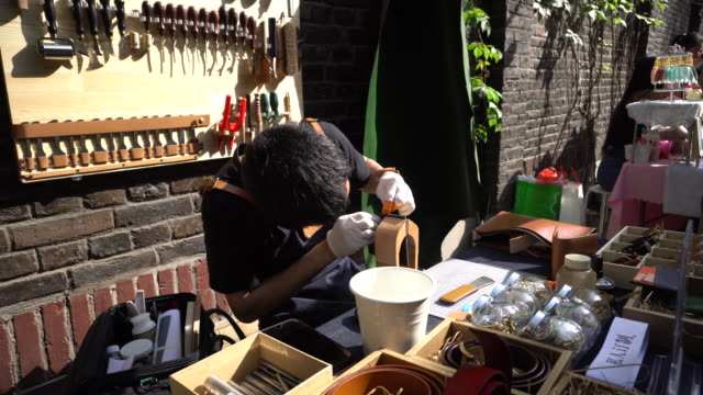 A young man is making leather craft product on an artisan fair held in an old hutong Homemade or handmade art and craft products become a popular...