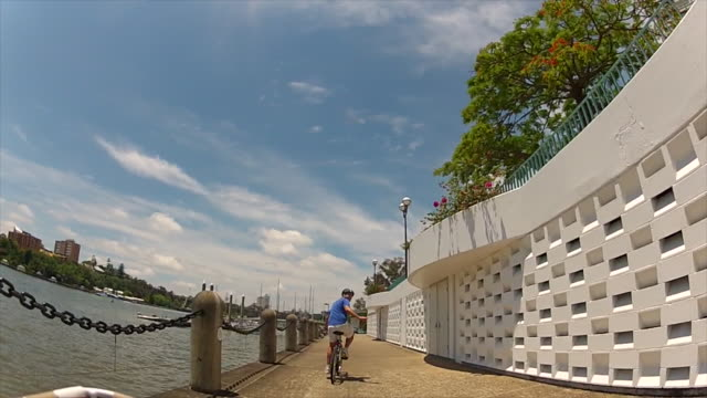 A young man is riding a bicycle through the city, in a river path, Brisbane (POV)