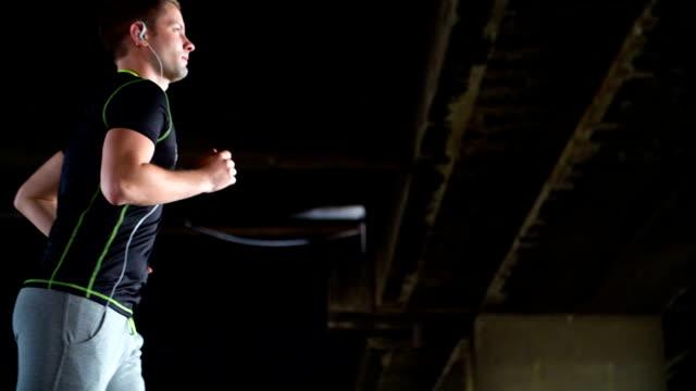 SLOWMO: Junger Mann Joggen Sie unter der Brücke.