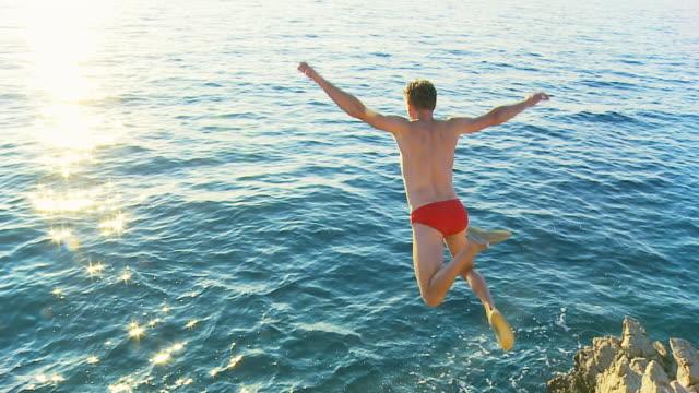 HD-ZEITLUPE: Junger Mann springt auf das Meer
