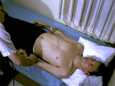 Young man laying on bed portable electrocardiogram machine in wooden case on adjacent table doctor enters frame removes attaches wires to terminals...