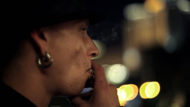 A young man lights a cigarette on a city street and turns to look at the camera.