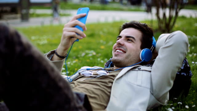 Young man listening music lying down outdoor