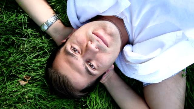 DOLLY: Junger Mann liegt auf Gras
