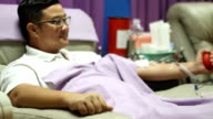 young man make relaxing himself on the sofa during giving blood