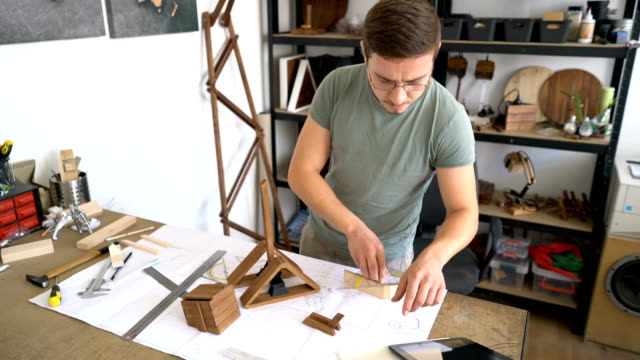 Young man measuring and assembling wooden parts for his craft project