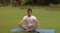ZI, CU, Young man meditating in park, Chattarpur, New Delhi, India