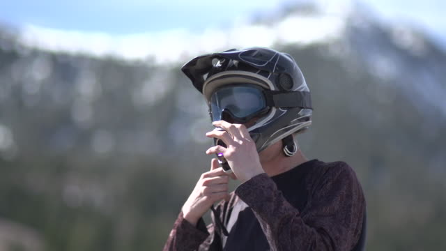 A young man mountain biker putting on his helmet.