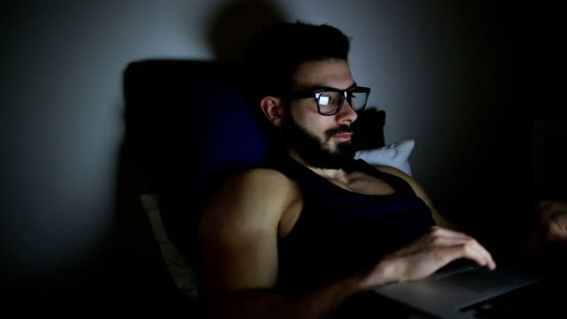 Young man on laptop at night