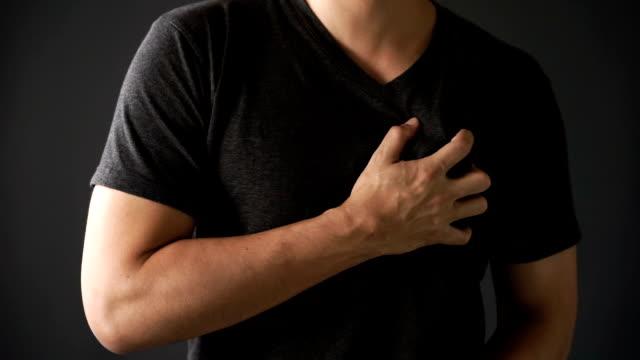 junger Mann schmerzhaft auf seinem Herzen