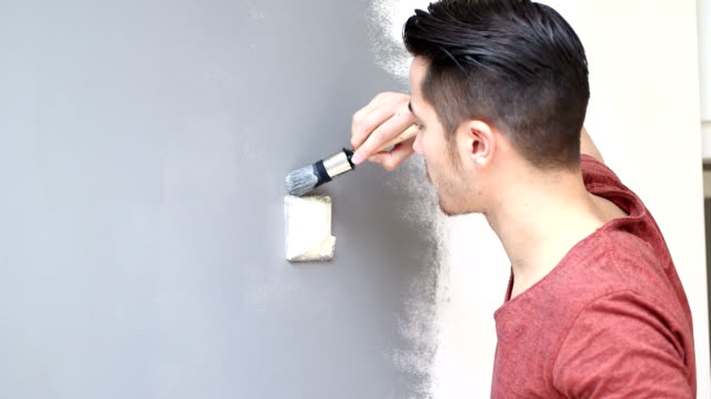 Young man painting wall with paintbrush