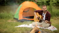 young man playing acoustic guitar on camping