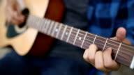 Young man playing guitar outdoors.