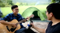 Young man playing guitar with friend in countryside-camping area, Chiang Mai, Thailand.
