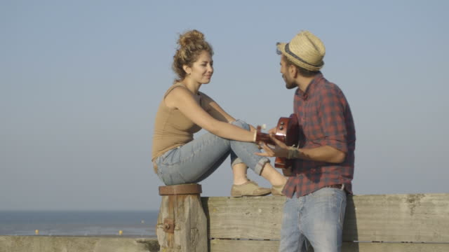 A young man playing guitar with woman