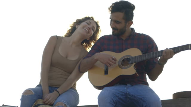 Young man playing guitar with woman