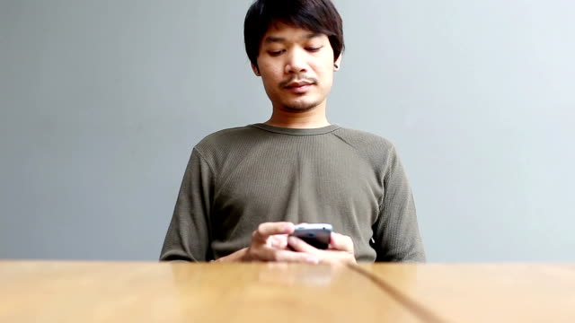 Young man playing smartphone at home