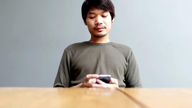 Junger Mann spielt smartphone zu Hause