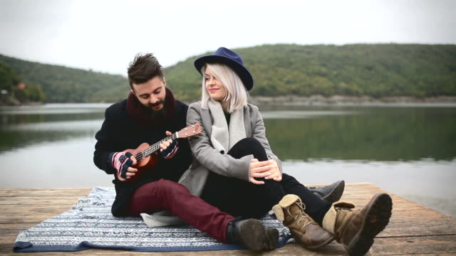 Young man playing ukulele to his girlfriend