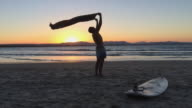 A young man playing with his towel, moving by the wind in a sunset at Byron Main Beach