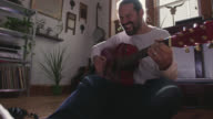 WS SLO MO. Young man plays acoustic guitar and sings in sunny apartment living room.