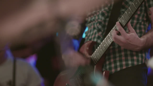 Young man plays guitar in band at crowded rock show