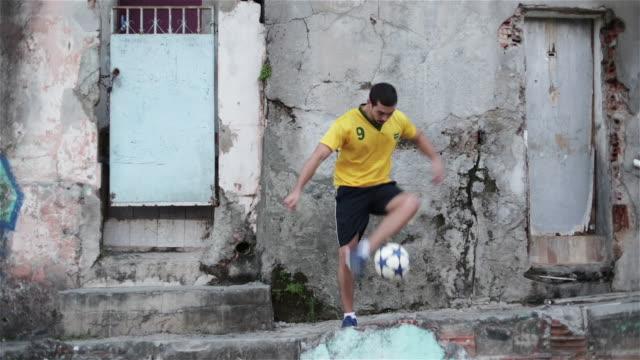 'WS A young man practices his football skills in a favela / Rio de Janeiro, Brazil'