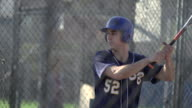 A young man practicing baseball at the batting cages.  - Slow Motion