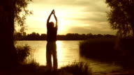 Young man practicing yoga near the river