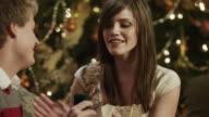 MS TD TU Young man presenting engagement ring to girlfriend sitting by Christmas tree / Cedar Hills,Utah,USA