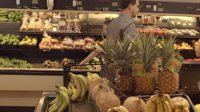 TS young man pushing shopping cart through produce section of food store while young woman and elderly man browse vegetable displays